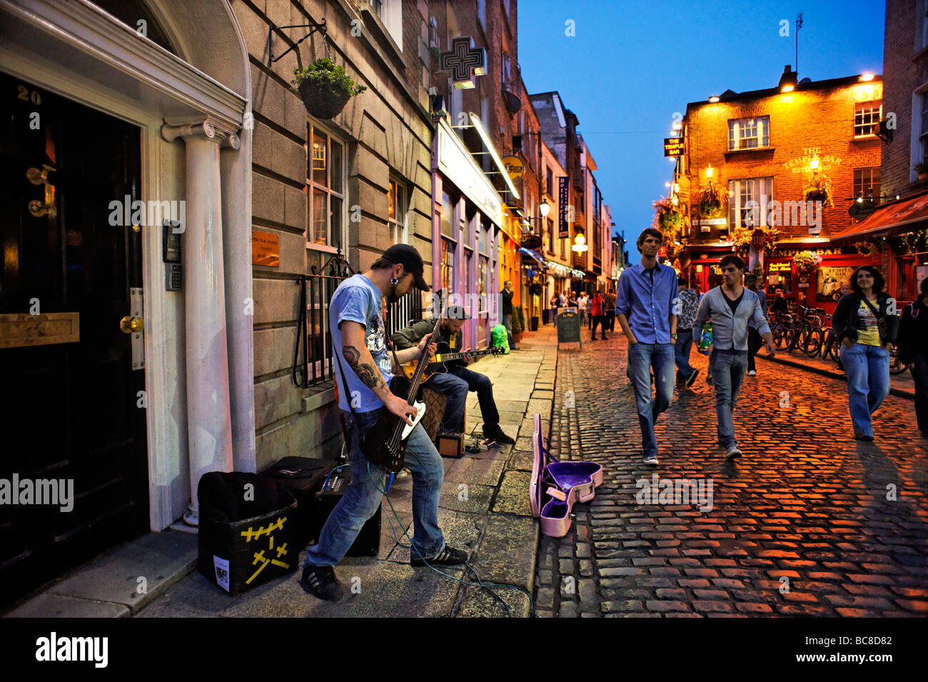 Band busking in cobbled street of Temple Bar nightlife area Dublin Republic of Ireland - Stock Image