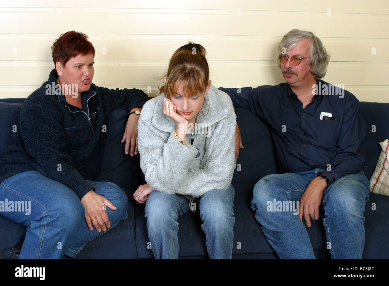 Teen years : Defiant teenage girl sit on the sofa between