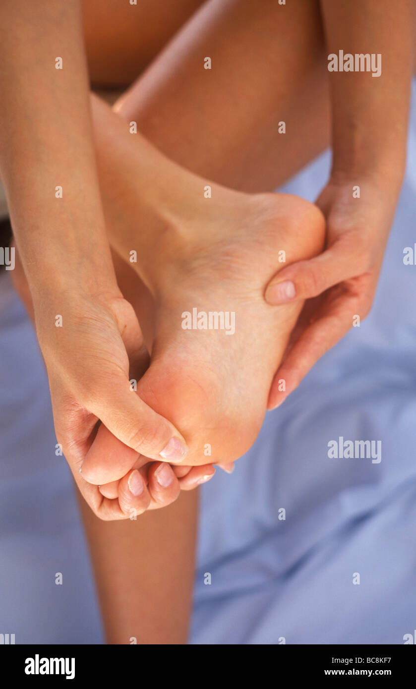 woman massaging her foot as if it is painful - Stock Image