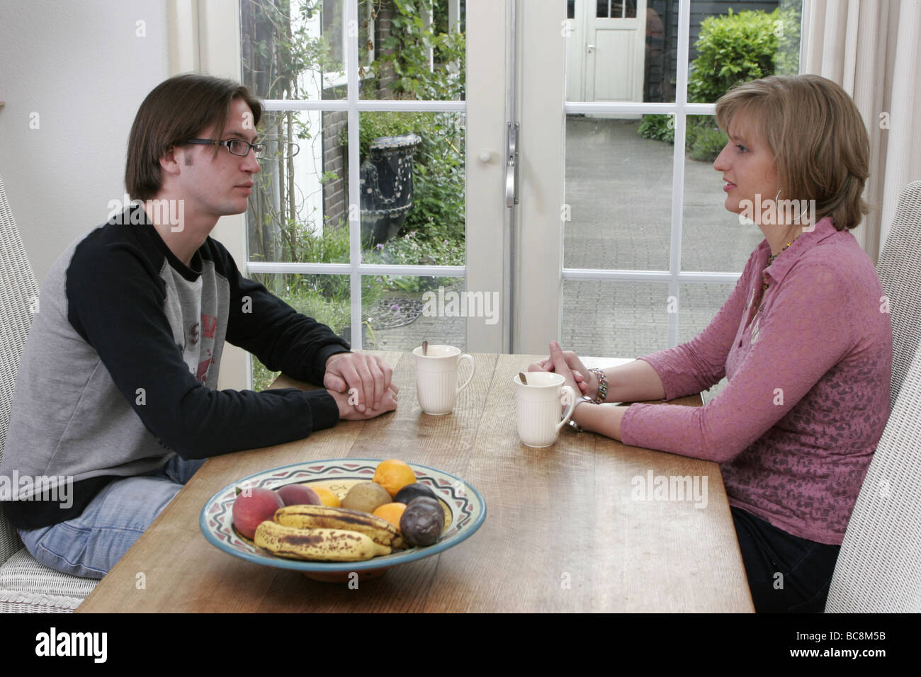 Young couple with cup of coffee sit at table having words - SerieCVS417416 Stock Photo