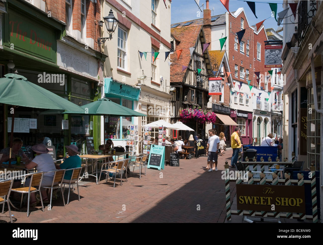 Shops and pavement cafes in George Street, Hastings Old Town, England - Stock Image