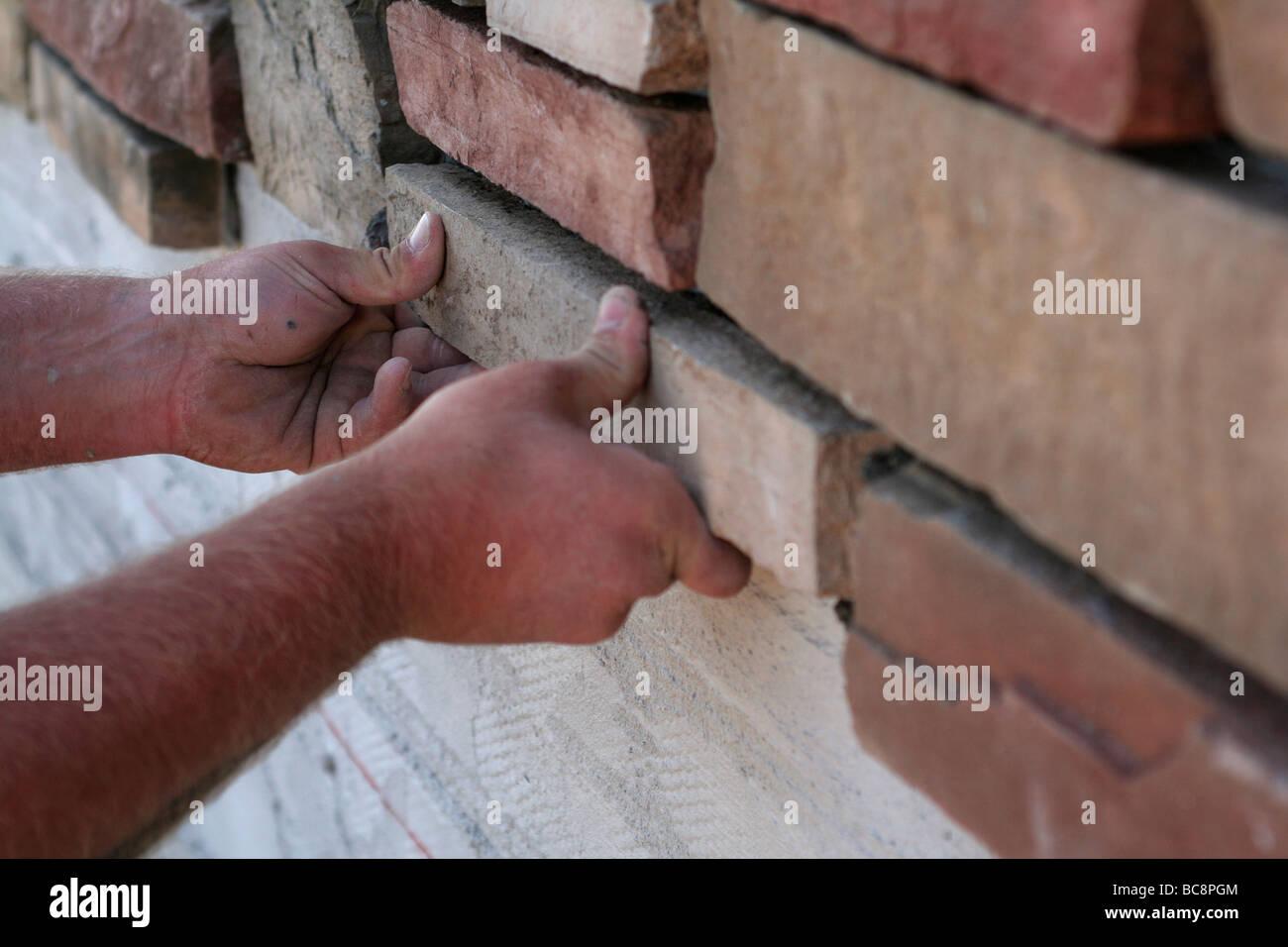 Mason placing facade stone on new home - Stock Image