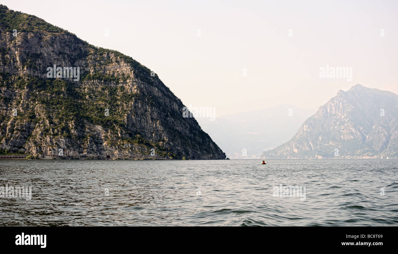 View over Lake Iseo towards a limestone rock formation with Monte Isola in the hazy background - Stock Image