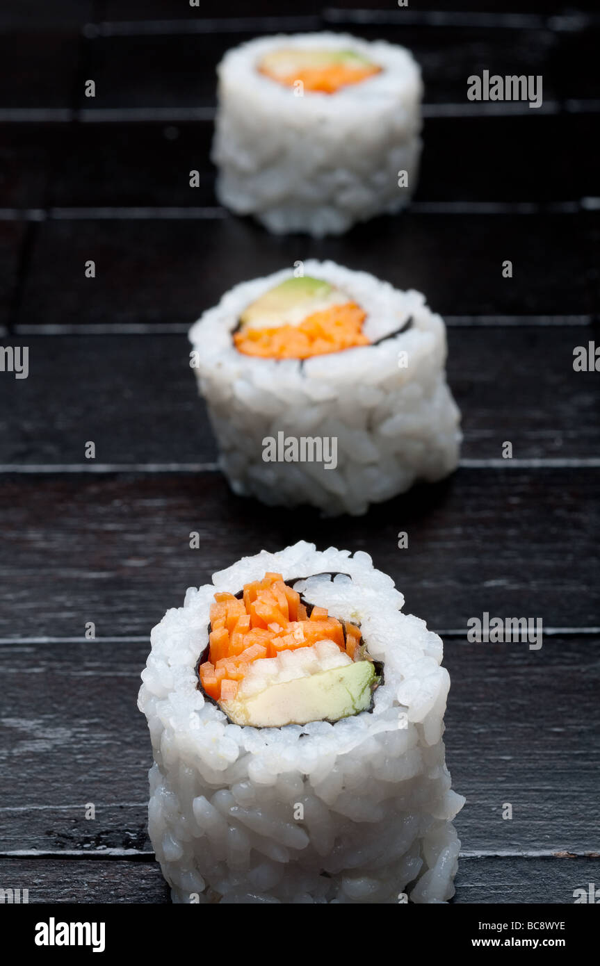shallow focus vertical macro of 3 rolls of sushi on black wood - Stock Image