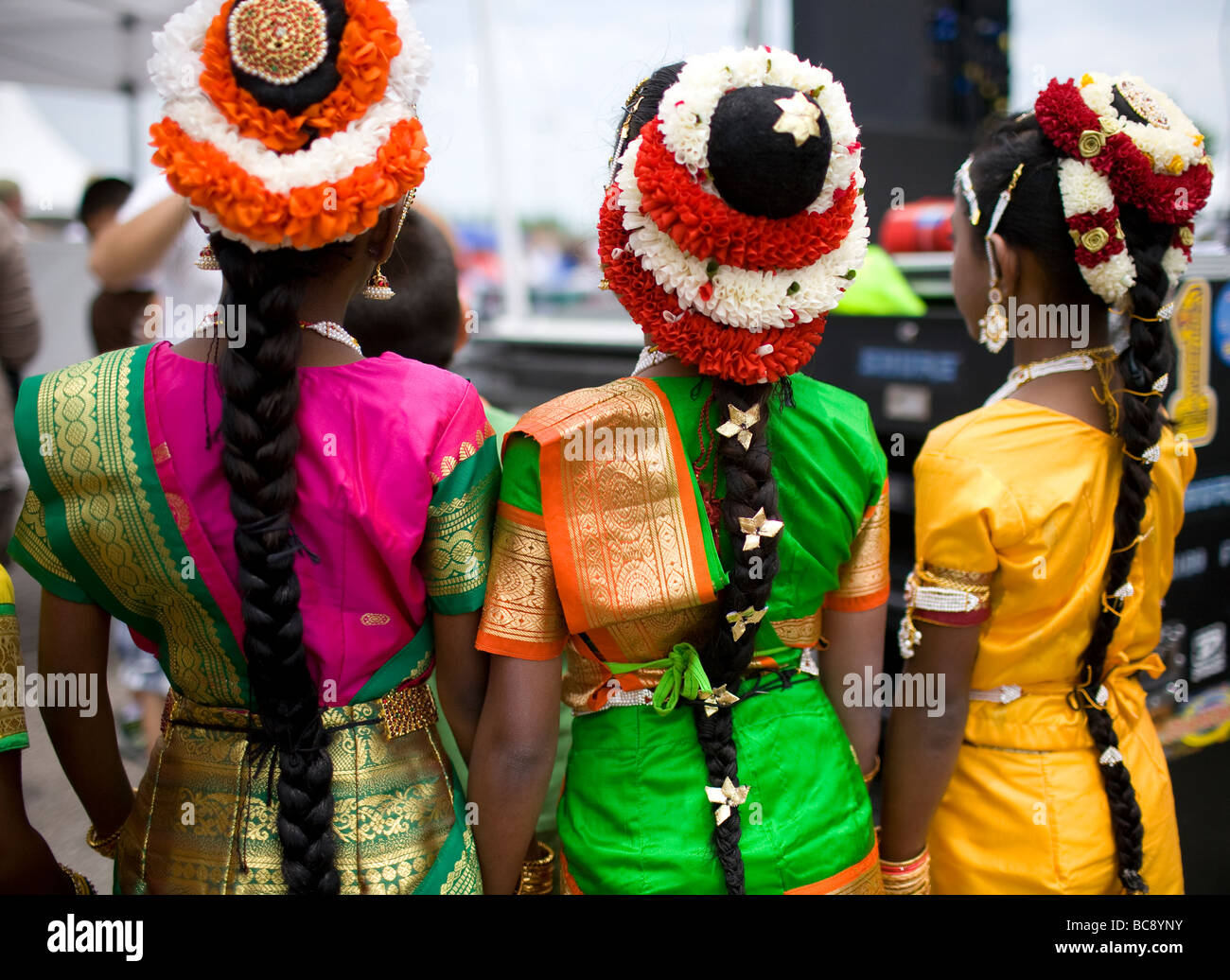 Three East Indian or Hindu girls wearing traditional headdresses waiting to perform at a festival. - Stock Image