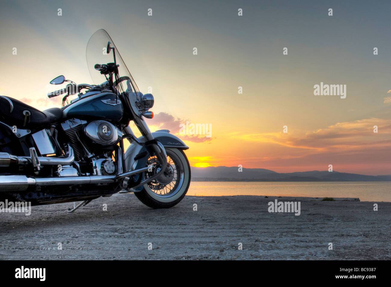 A harley davidson motorbike motorcycle taking in the sunset as the sun goes down on the day - Stock Image