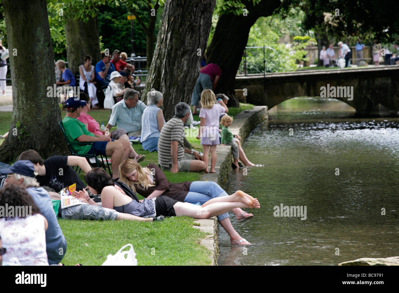 People sunbathing on the banks of the River Windrush in Bourton-on-the-Water, Gloucestershire, UK - Stock Image
