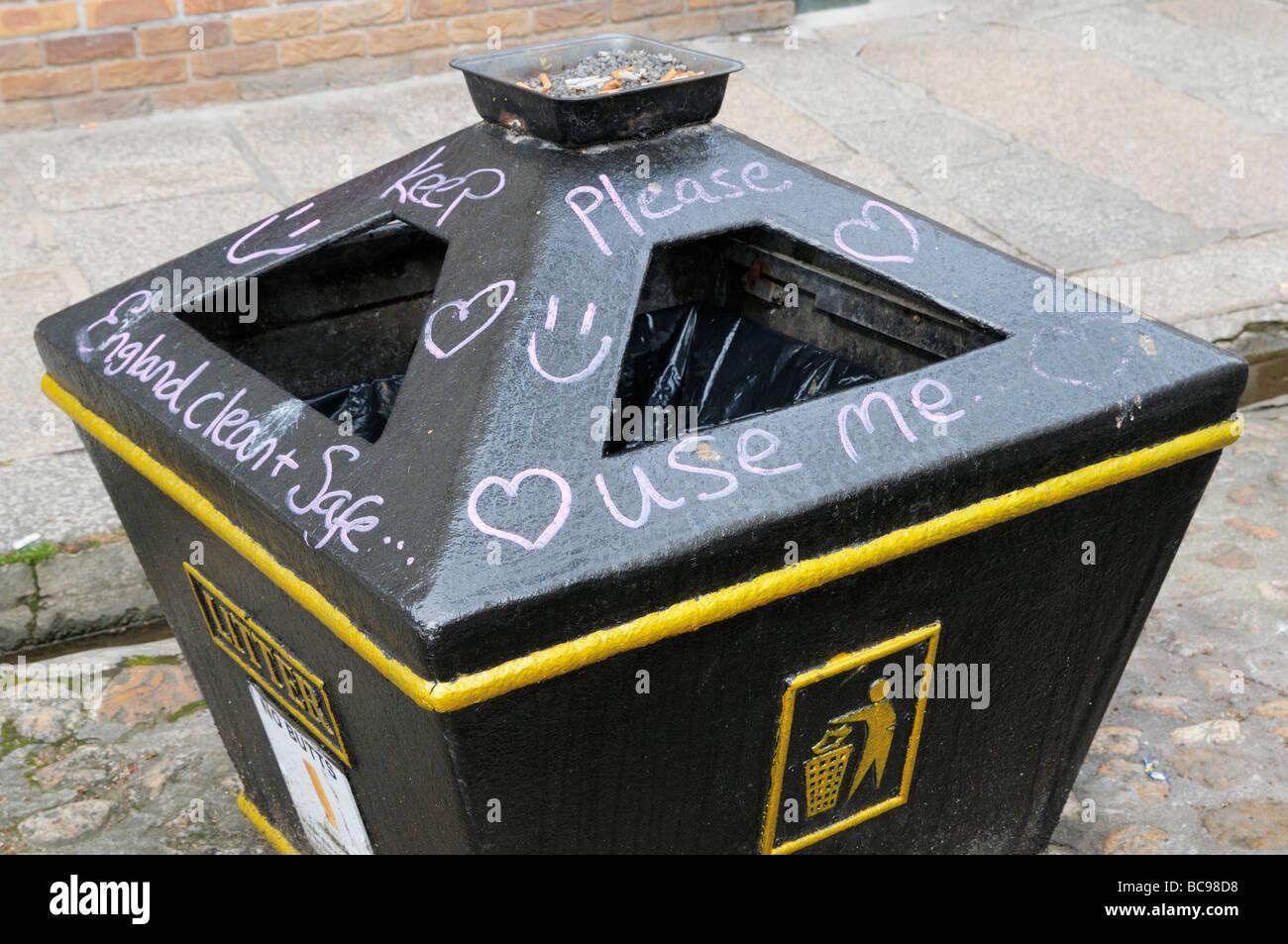 Public litter bin covered in graffiti message - Stock Image