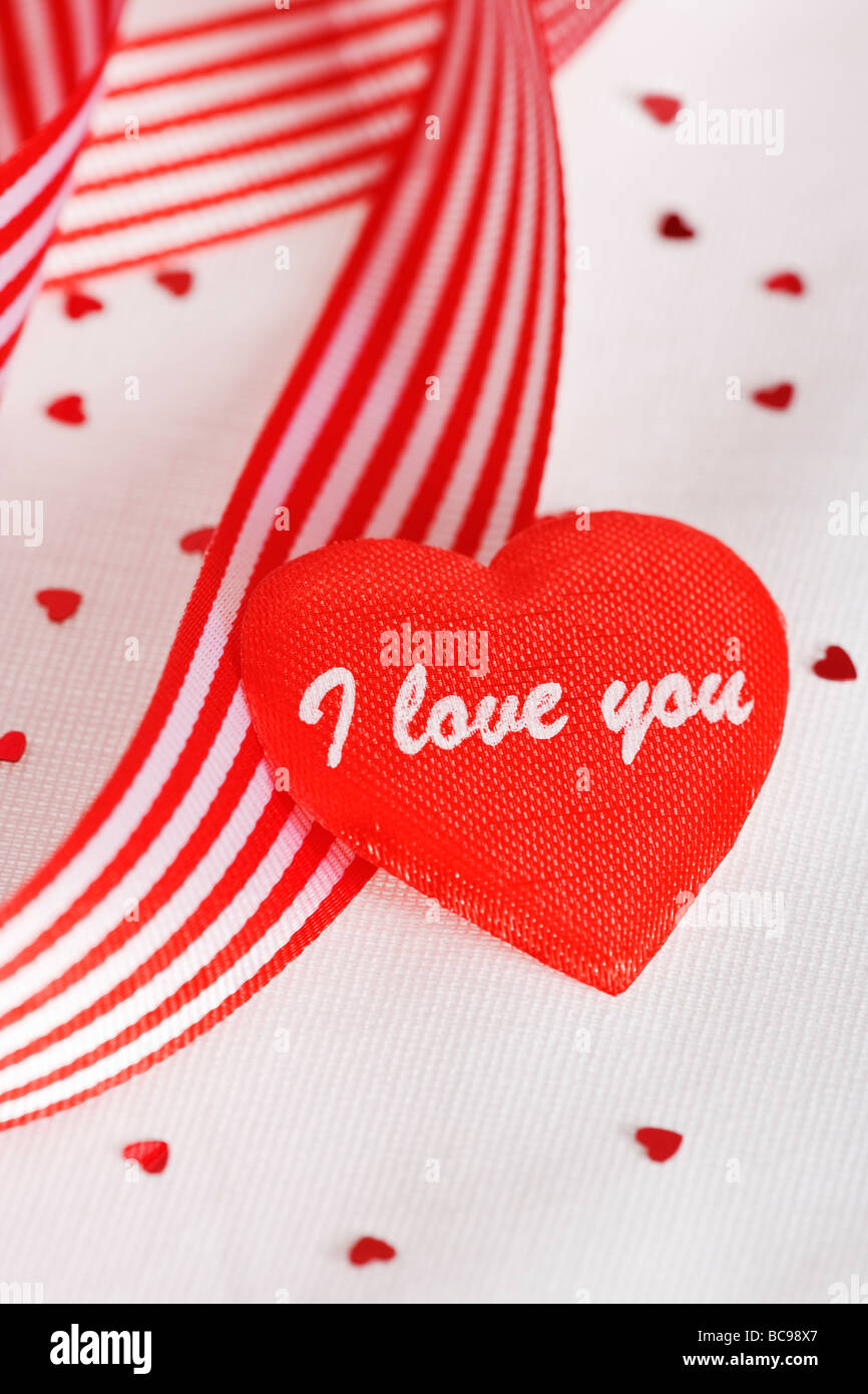 I Love You love heart with red and white striped ribbon Valentines day theme against white background - Stock Image
