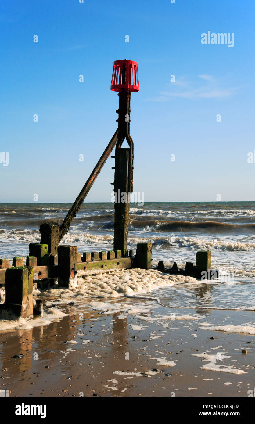 Breakwater marker post and trapped spume at Mundesley, Norfolk, United Kingdom. - Stock Image