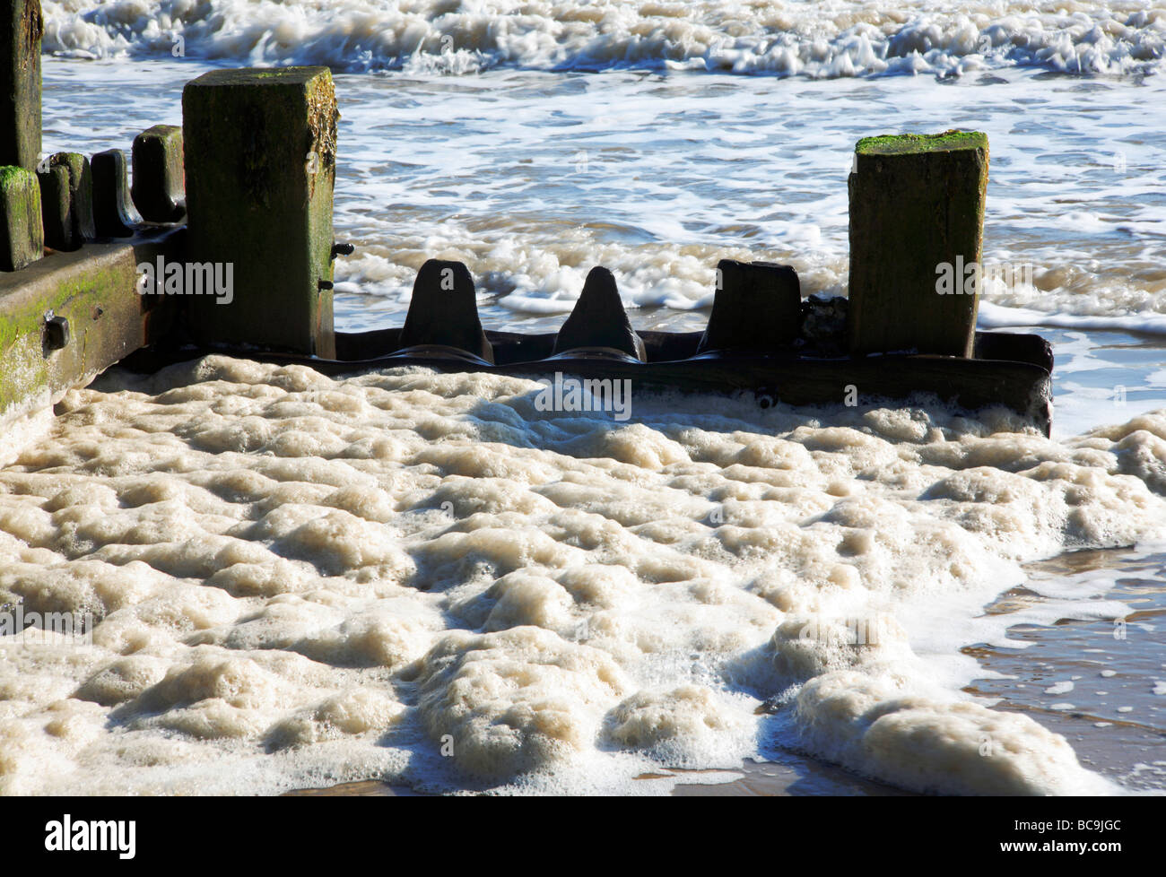Spume collecting by a breakwater at Mundesley, Norfolk, United Kingdom. - Stock Image
