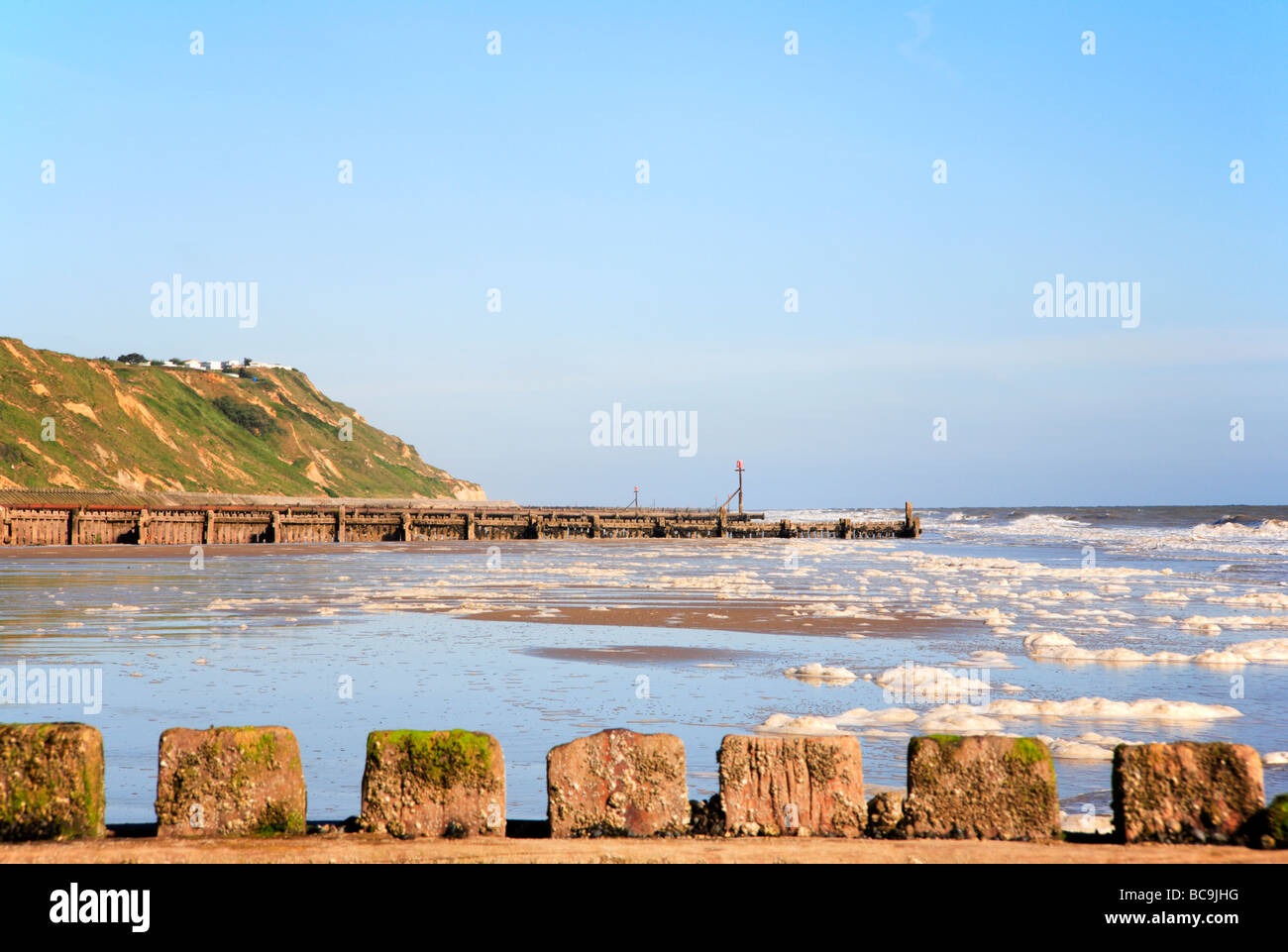 West beach at Mundesley, Norfolk, United Kingdom, with ougoing tide and spume. - Stock Image
