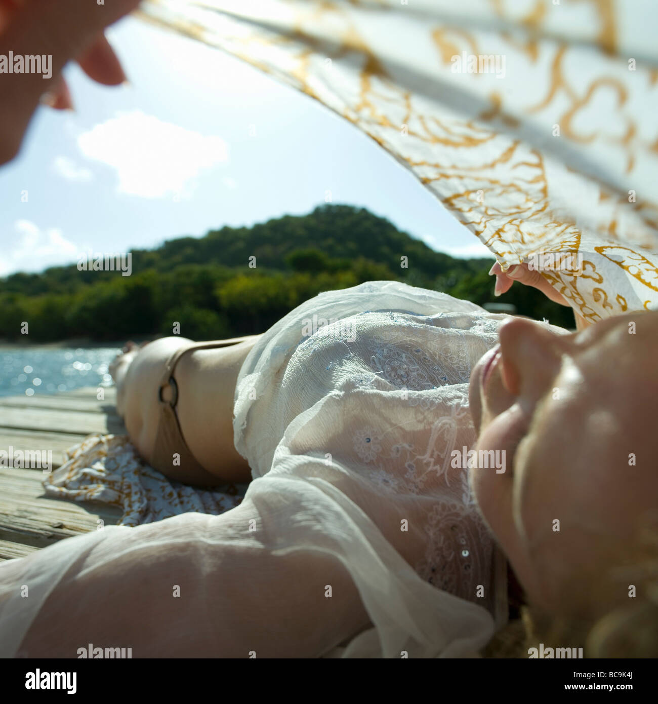 Young couple on poolside holding sarong up in wind - Stock Image