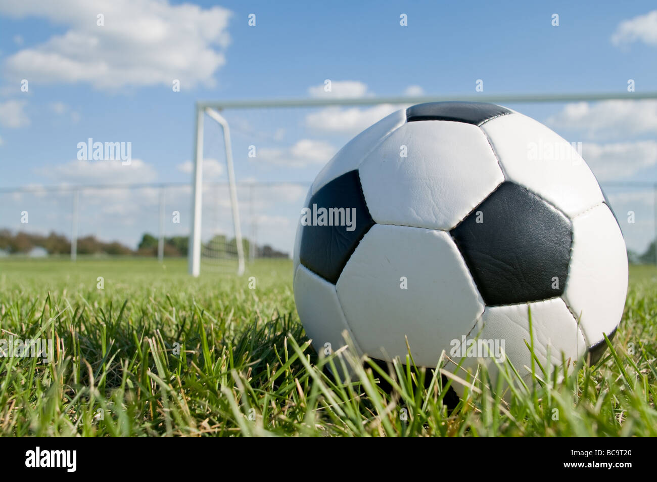Soccer Backgrounds Stock Photo: Soccer Ball On The Pitch Field With Goal In Background