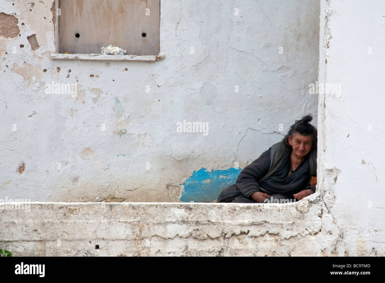 Old tramp lady trying keep warm against a cold damp wall in Argostoli in Kefalonia greek island - Stock Image