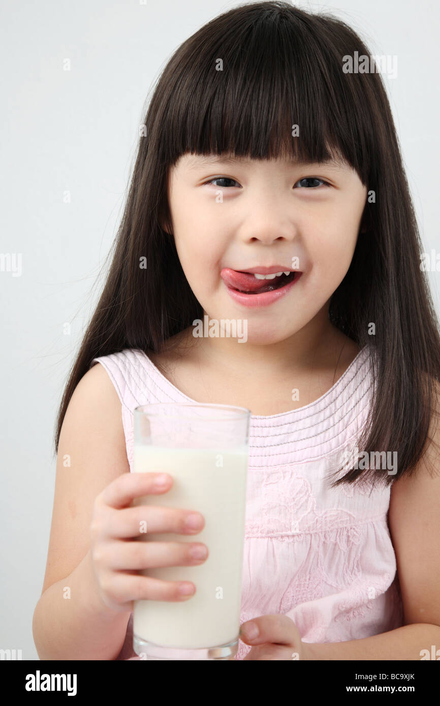 little chinese girl holding a glass of milk - Stock Image