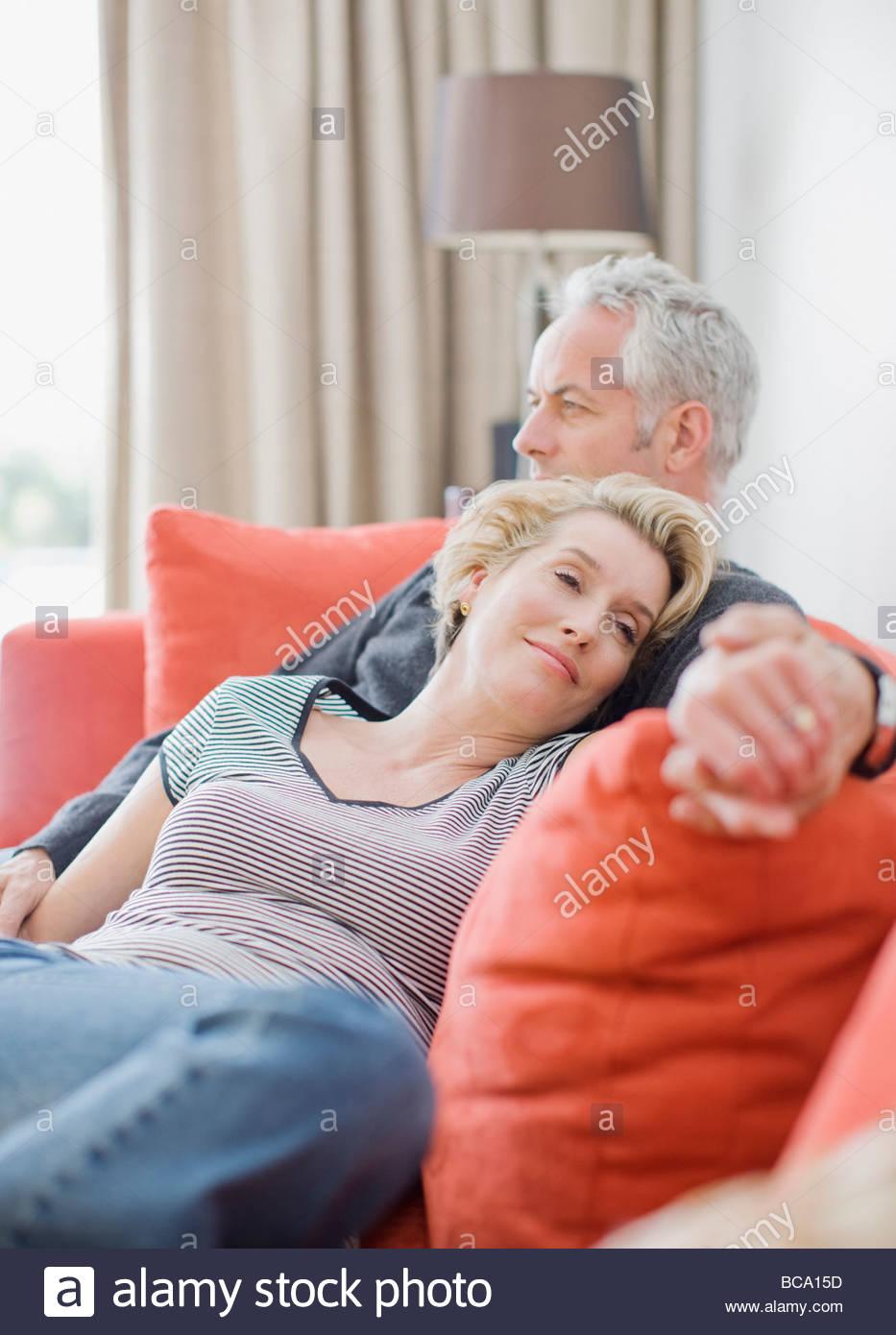 Couple laying on sofa - Stock Image