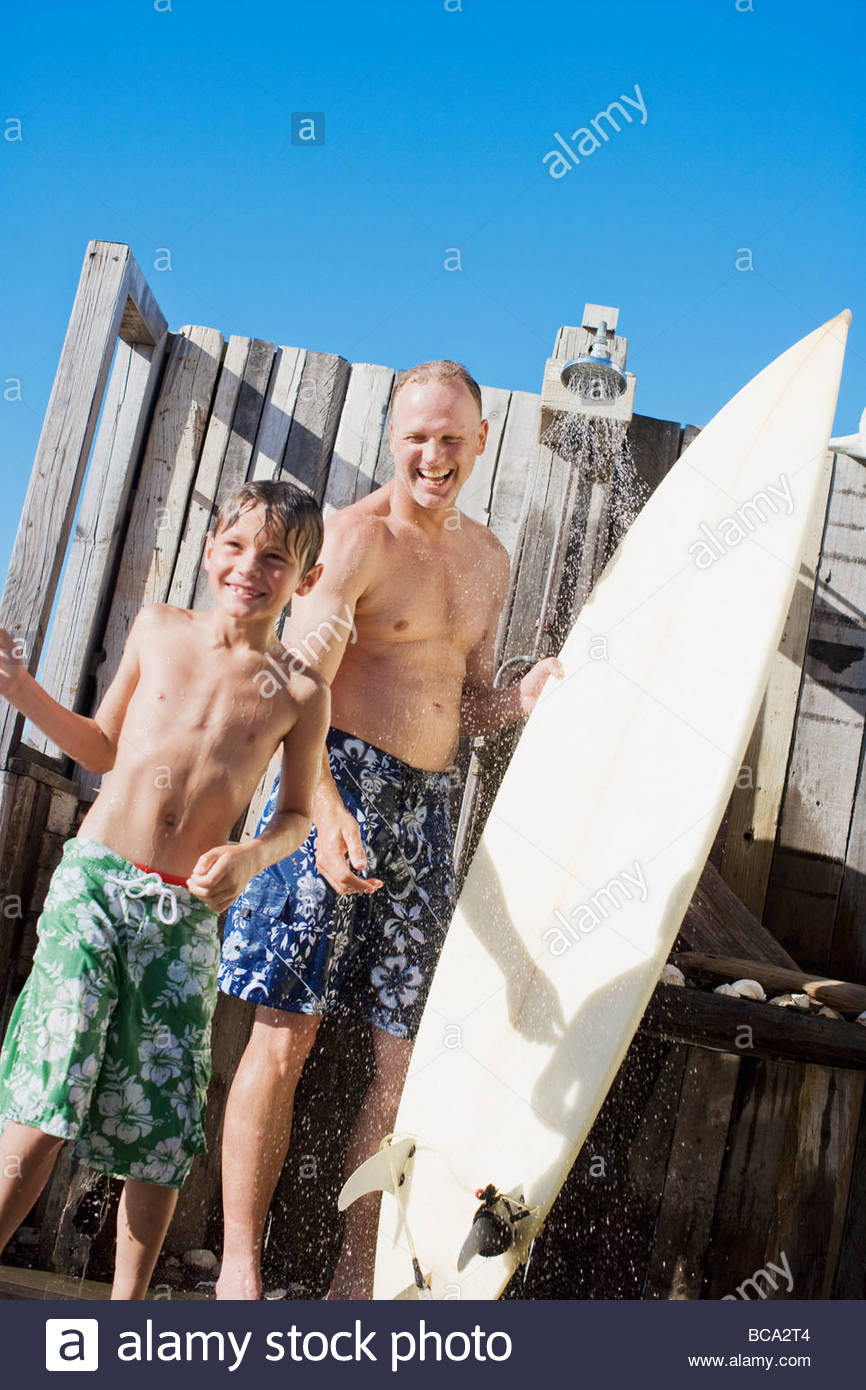 Father and son with surfboard rinsing off outdoors - Stock Image