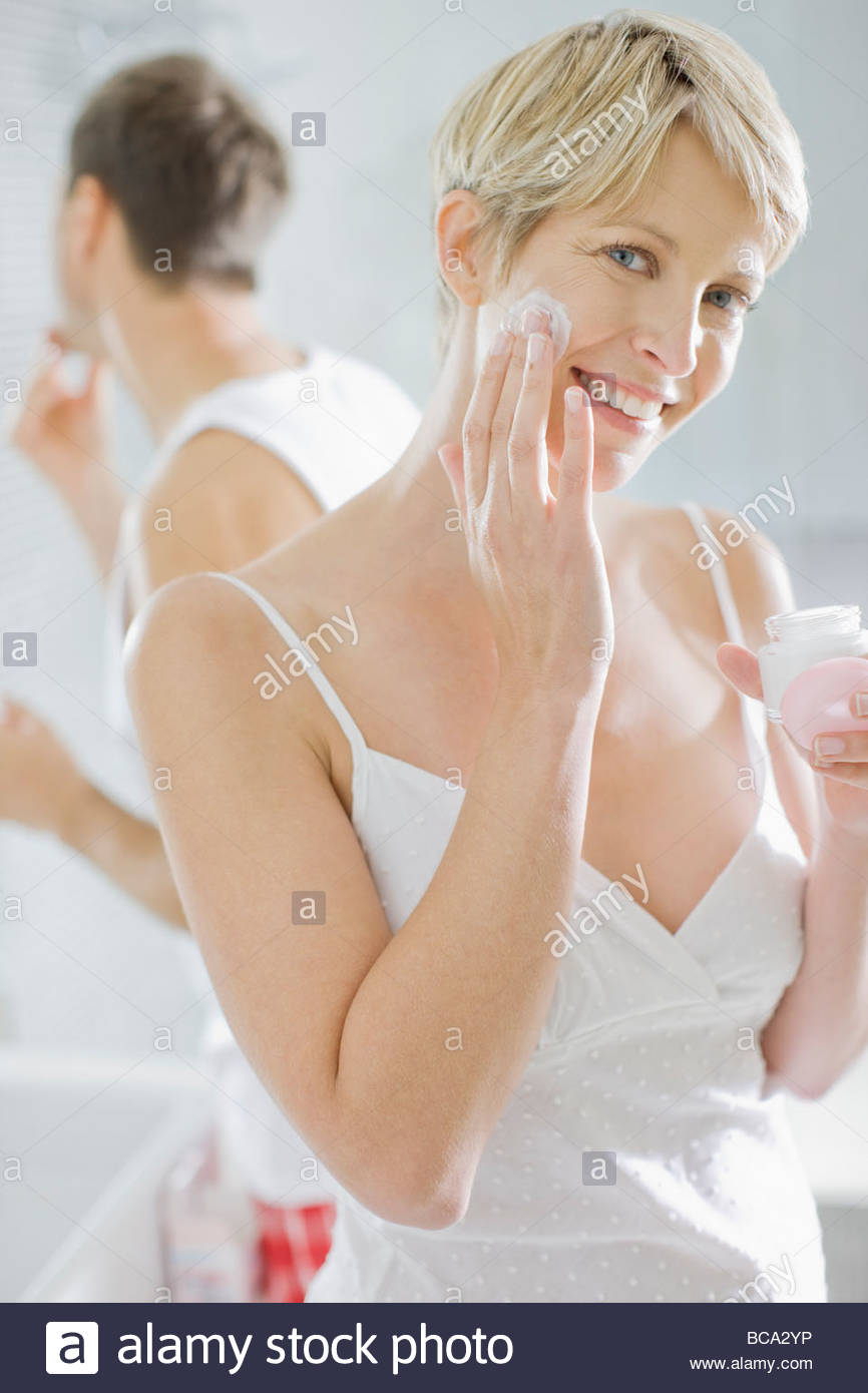 Woman applying face cream in the morning - Stock Image