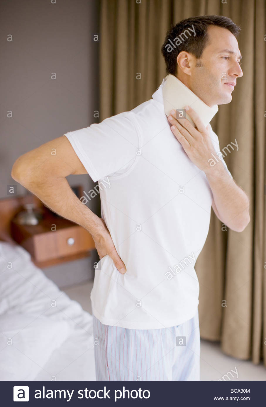Man with neck brace and aching back - Stock Image