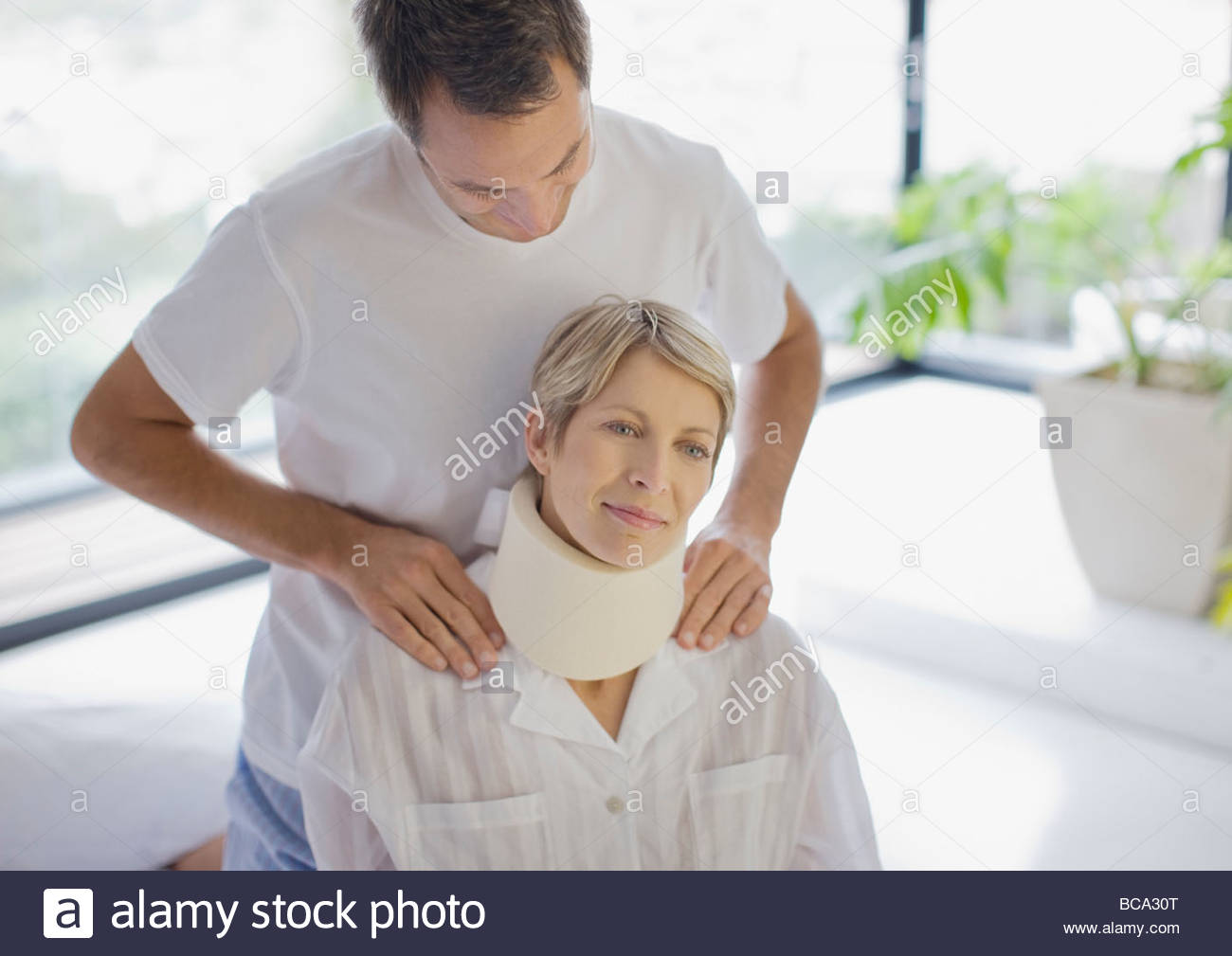 Husband helping wife in neck brace - Stock Image