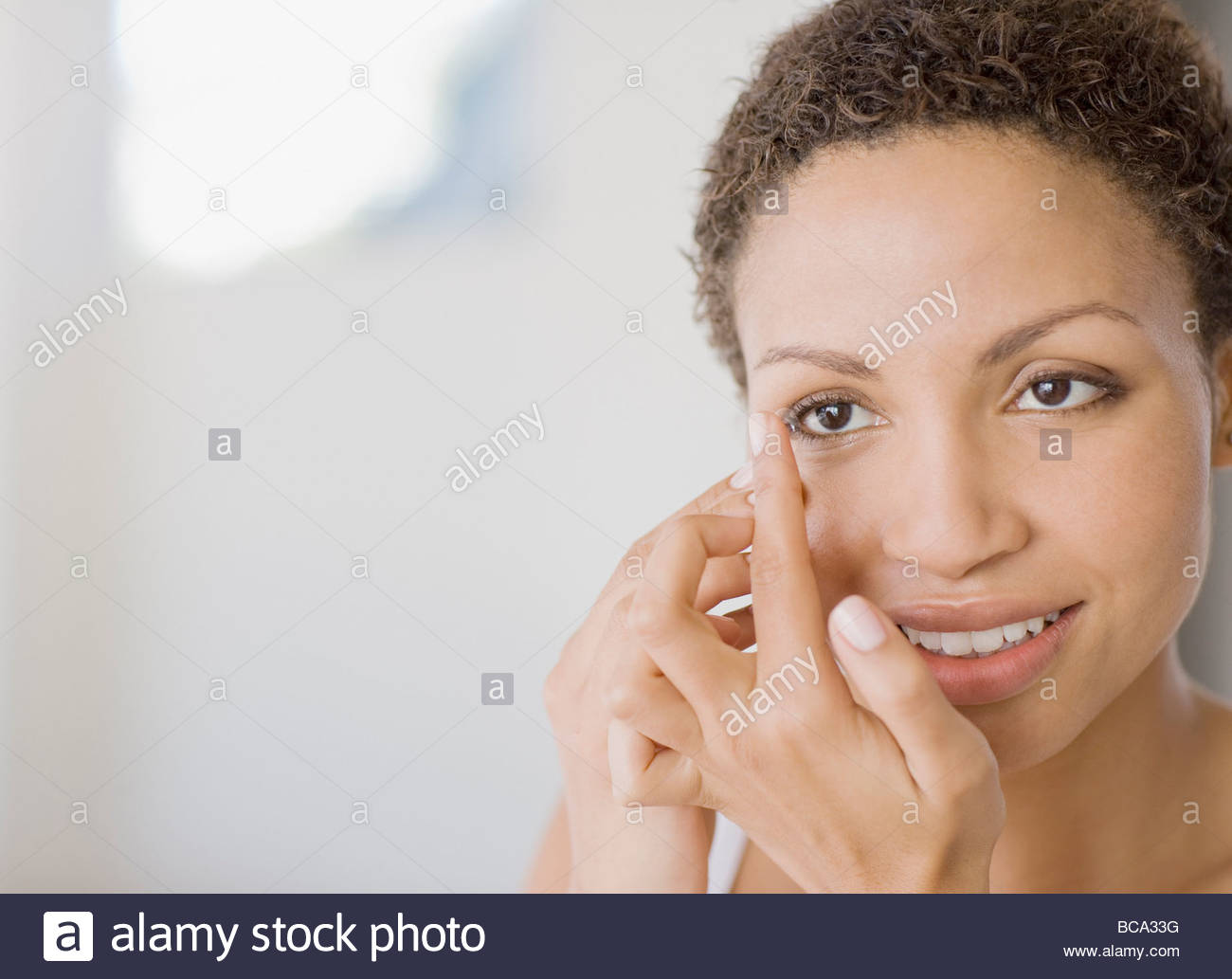 Woman inserting contact lens - Stock Image