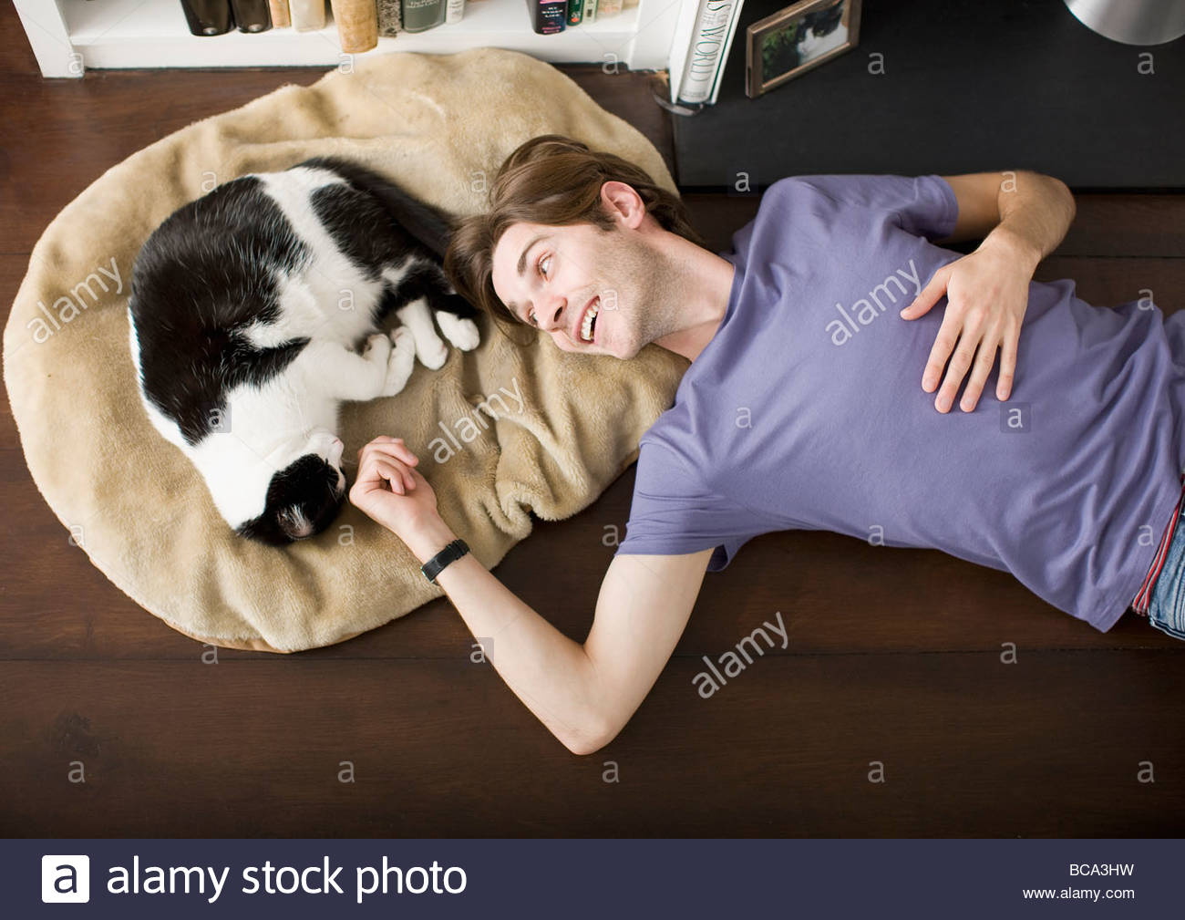 Man laying on floor with cat - Stock Image