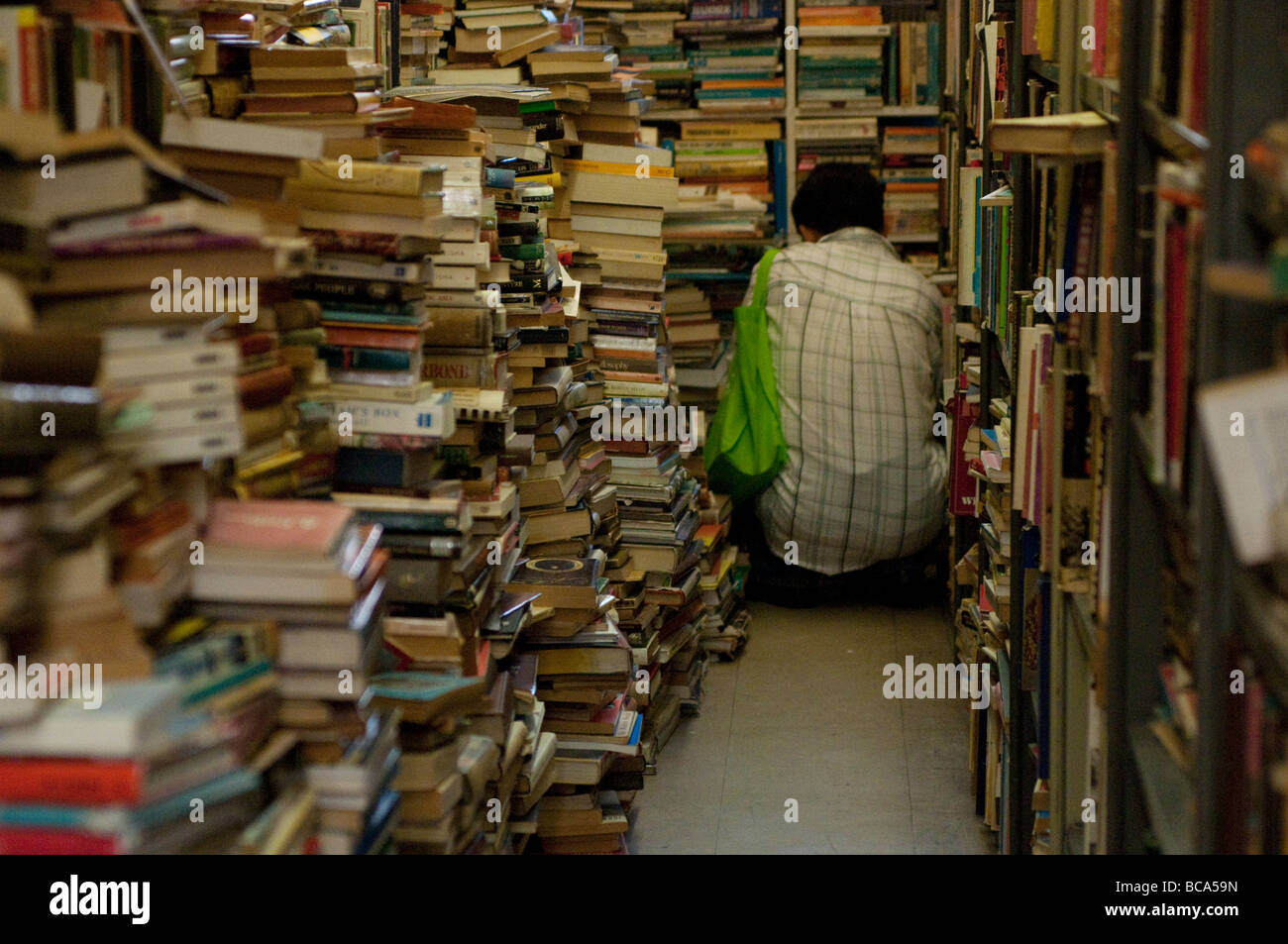 Man browsing in Gould's secondhand bookshop on King Street, Newtown, Sydney NSW Australia - Stock Image