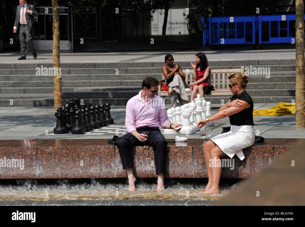 City of London workers take to the outside spaces during their lunch break in the heatwave - Stock Image