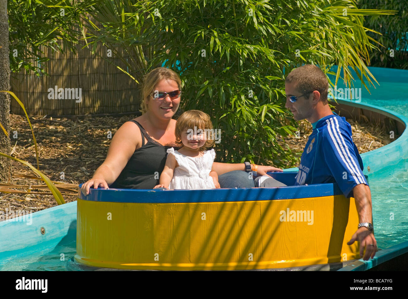 Mother Father and Young Baby Daughter On An Amusement Park Water Ride - Stock Image