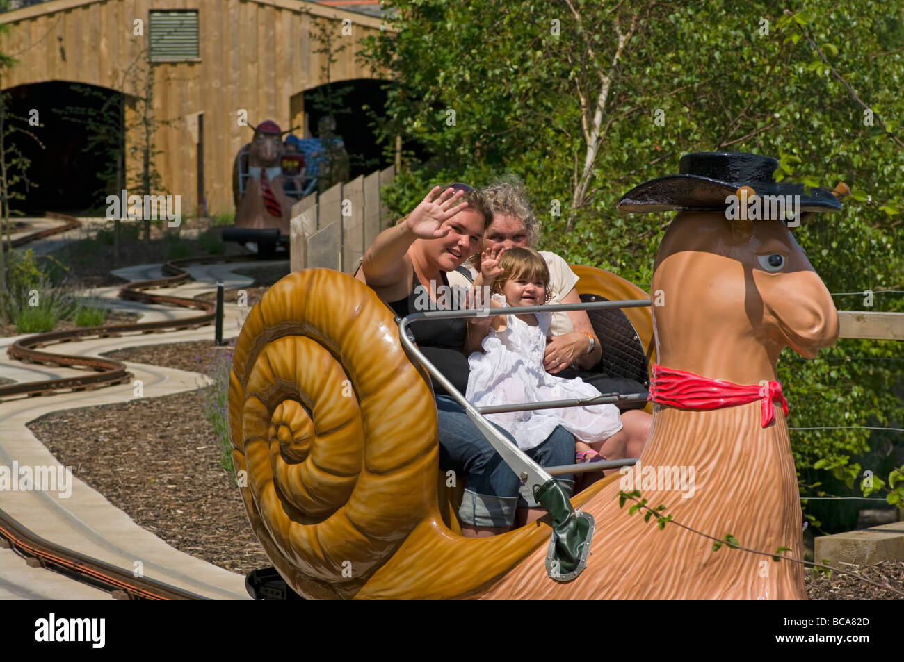 3 Generations Riding an Amusement Park Snail Ride - Stock Image