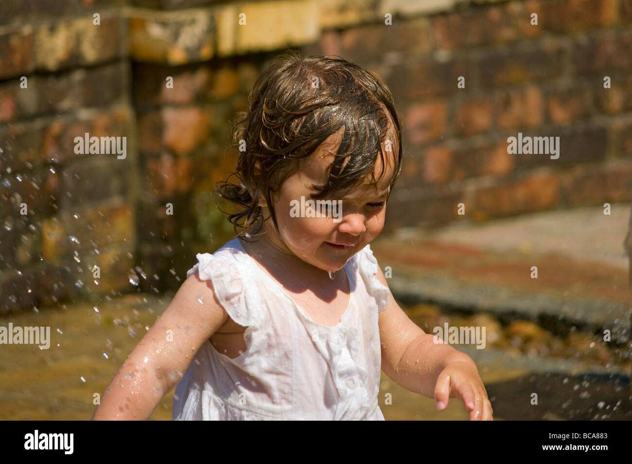 Baby Girl In a White Dress Playing In a Water Fountain - Stock Image
