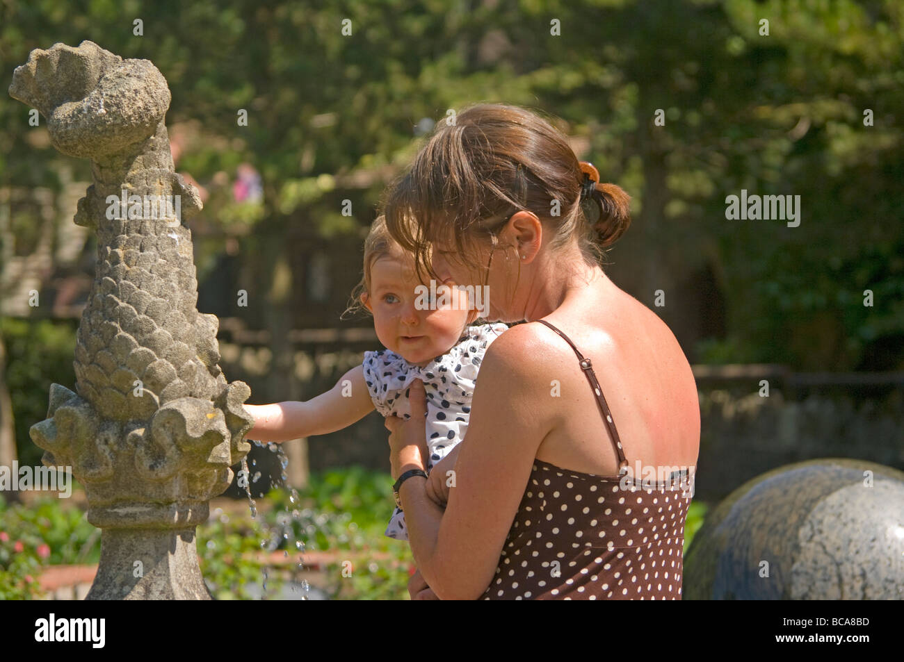Grandmother and Granddaughter Playing With A Water Fountain - Stock Image