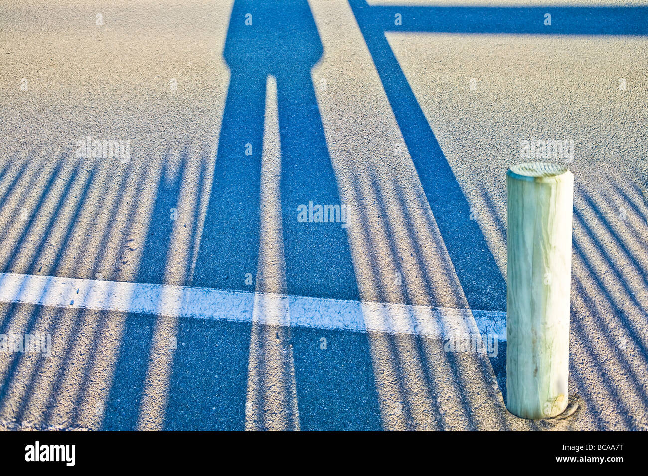 long shadows of a pair of legs and fence on asphalt - Stock Image