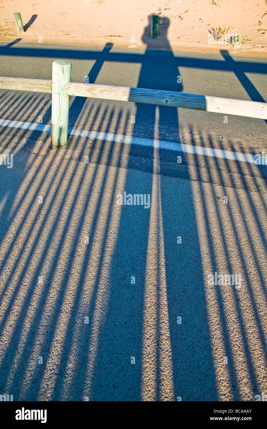 long shadows of a human silhouette and fence on asphalt - Stock Image