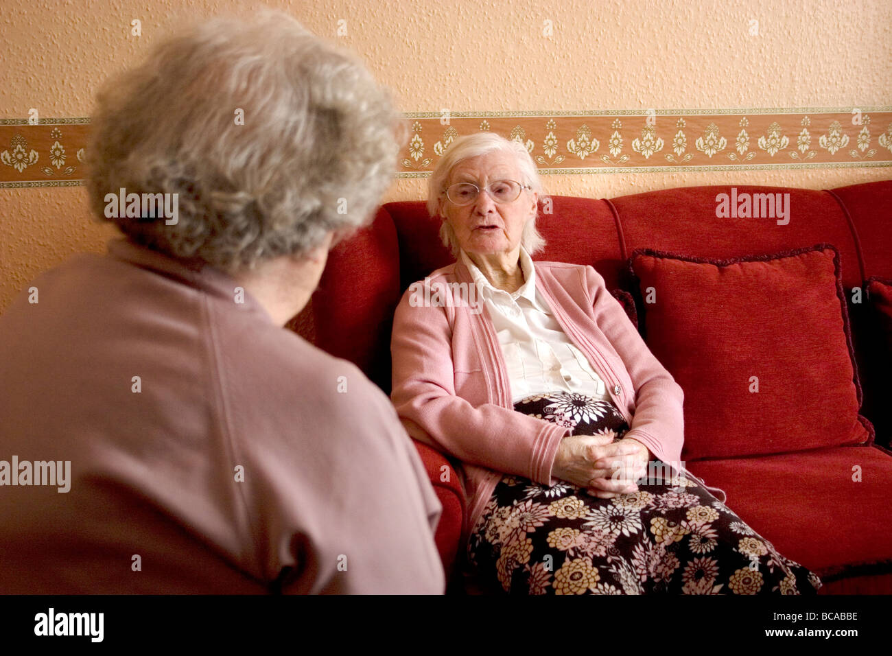 two elderly ladies at home having a conversation - Stock Image