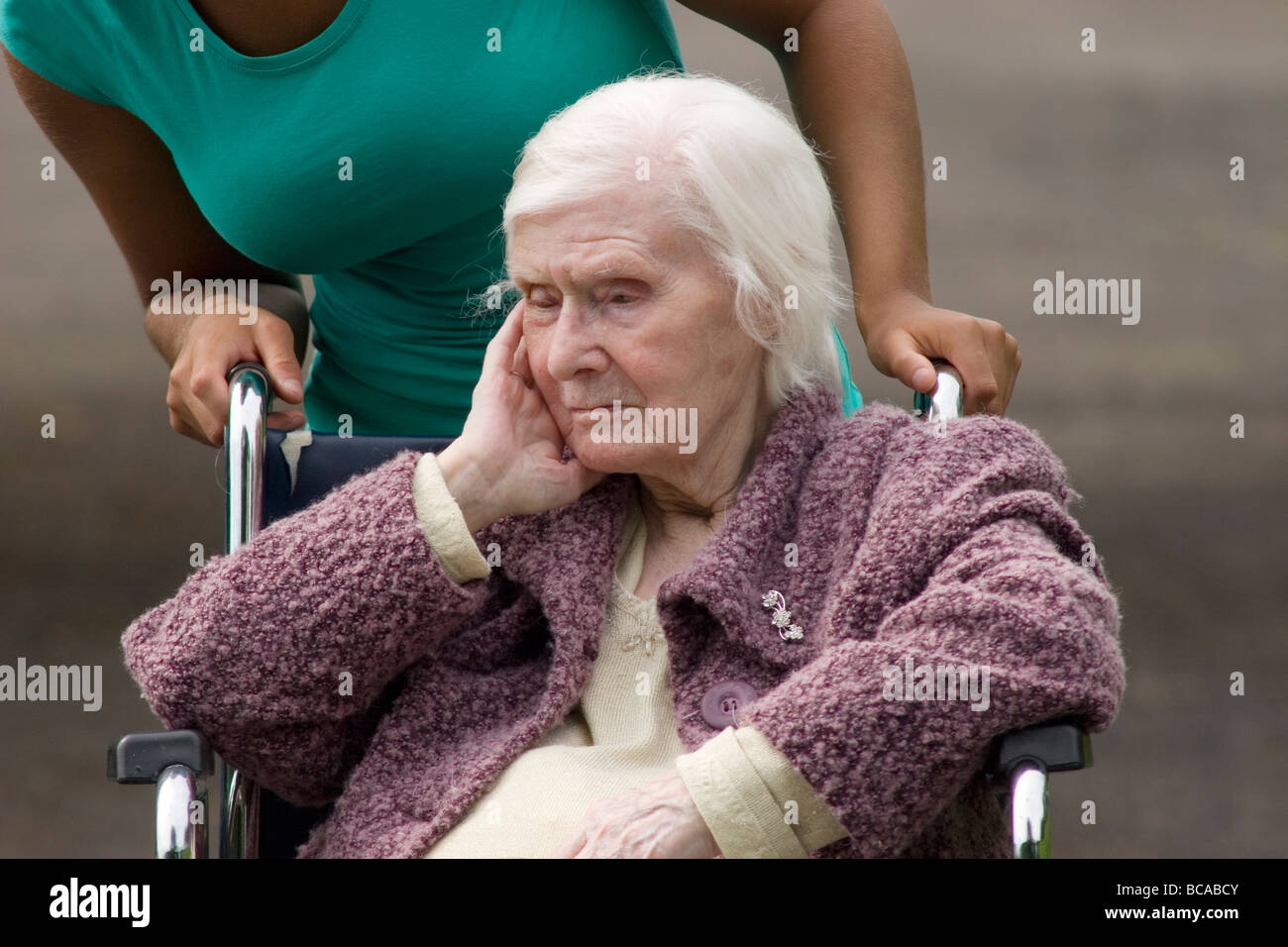 unhappy geriatric lady being pushed in wheelchair by woman - Stock Image