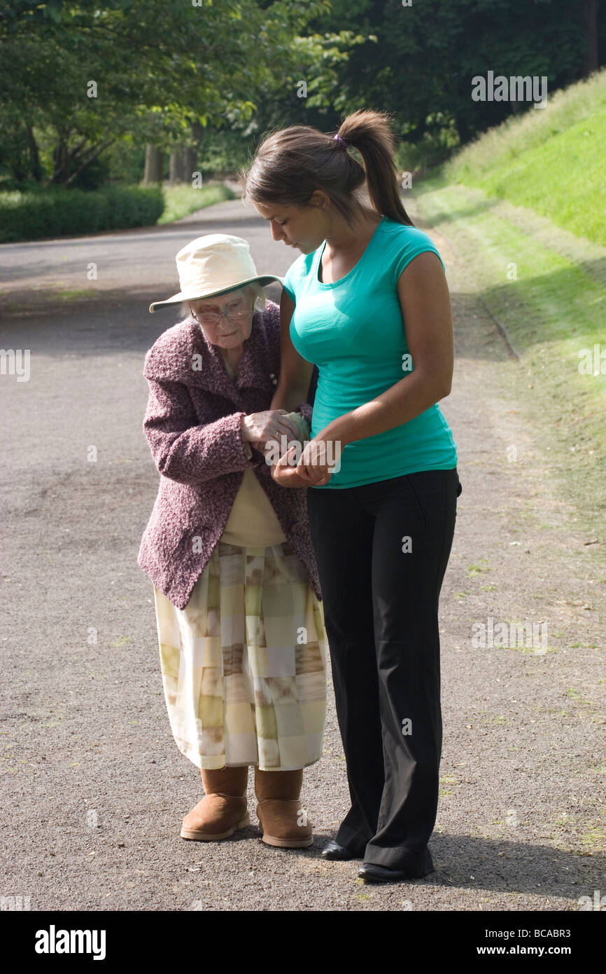young woman walking with very elderly lady in park - Stock Image