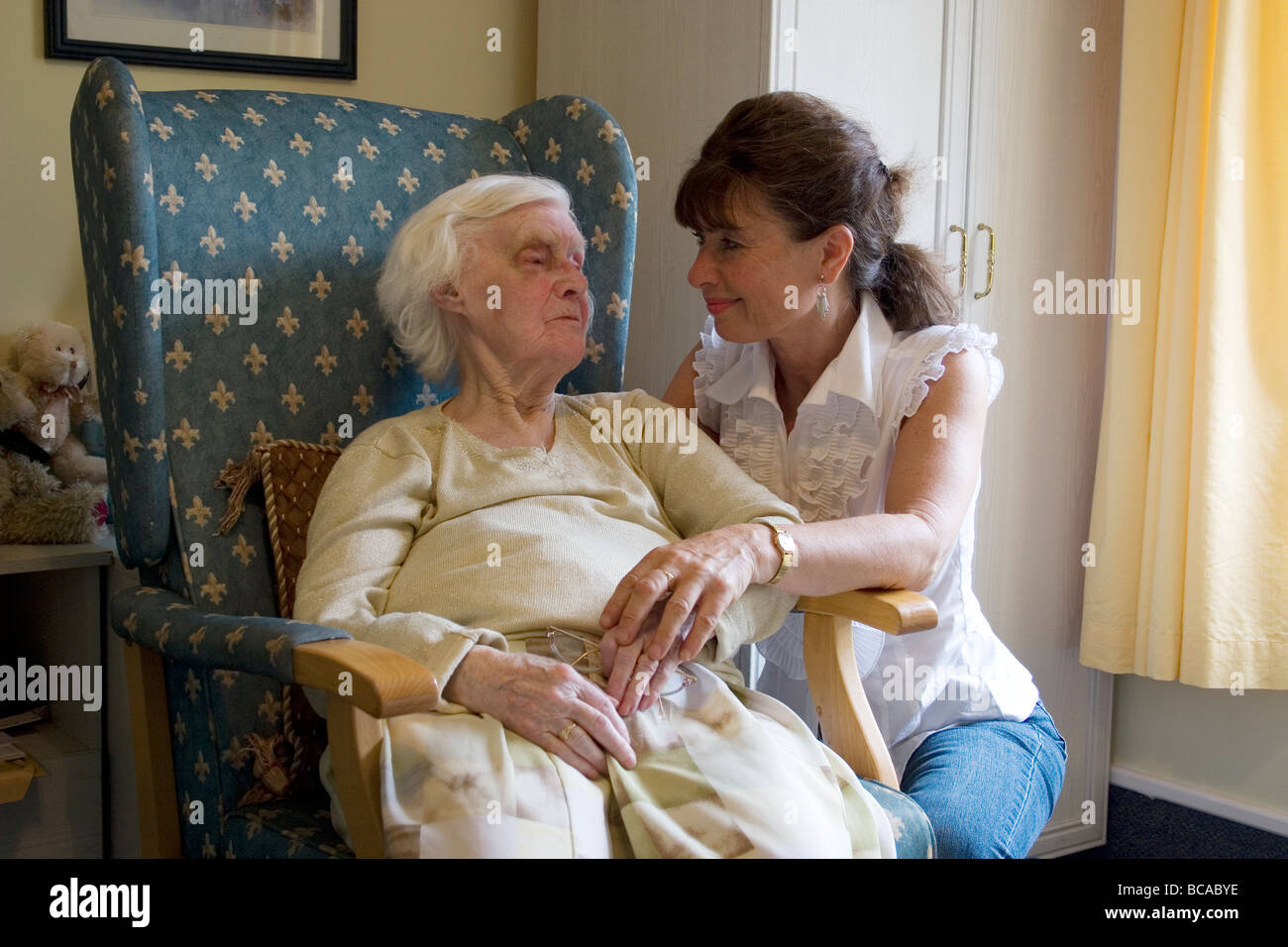 woman consoling dying old lady with bruised eye in nursing home - Stock Image
