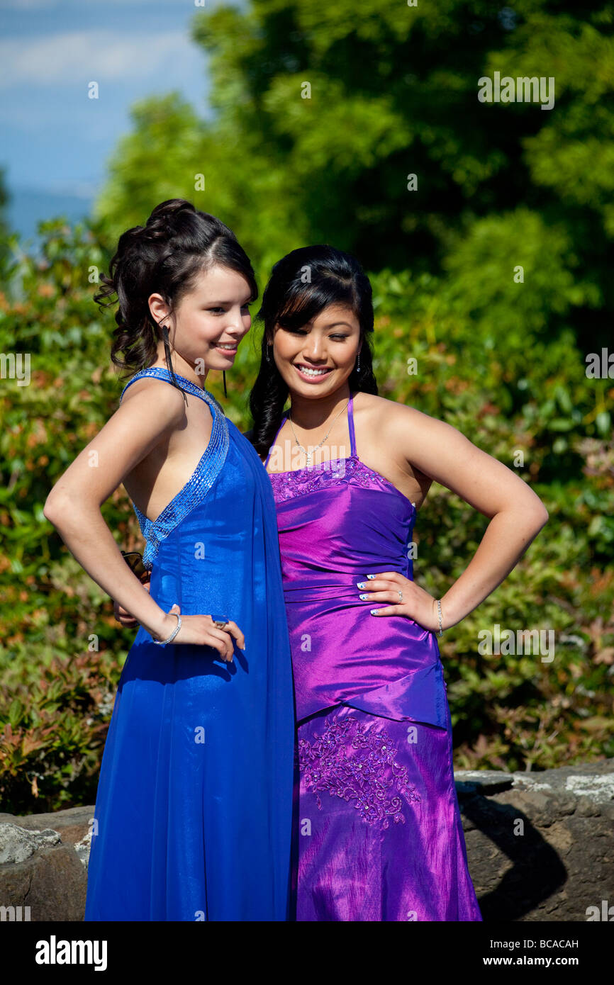 two girls in formal dress for school prom posing for photographs at ...
