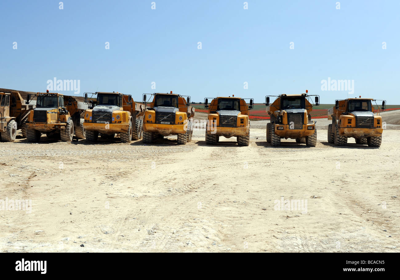 Line up of earth moving vehicles in a dusty building site of Brighton football stadium - Stock Image