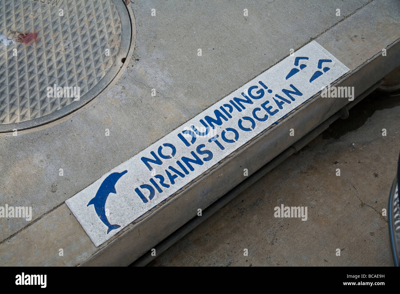 Painted sign on curb warns about dumping into drain - Stock Image