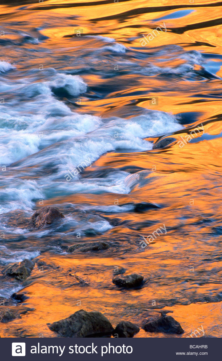 Scenic of moving water reflecting sunlit canyon walls - Stock Image