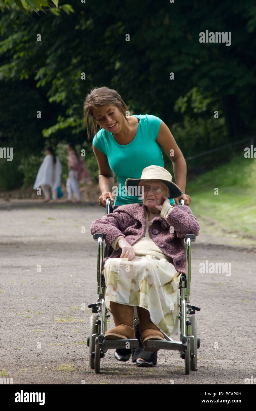 young woman pushing elderly lady in wheelchair in park - Stock Image