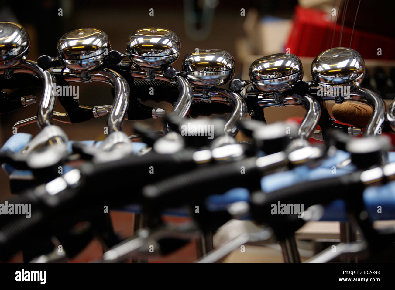 Handle bars with bicycle bells waiting to be attached to bicycles at Pashley Cycles in Stratford-Upon-Avon, Warwickshire, - Stock Image