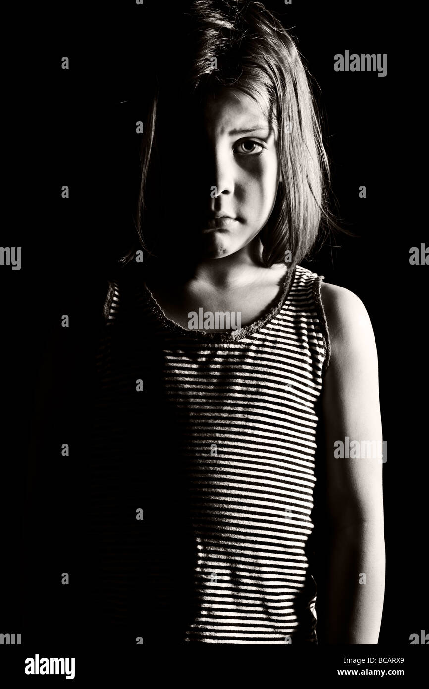 Low Key Shot of a Sad Looking Child Looking Directly into the Camera - Stock Image