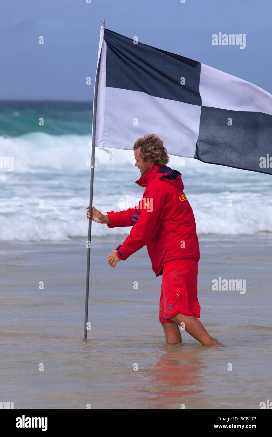 RNLI Lifeguard plants flag in waves off Porthmeor beach in summer sun St Ives Cornwall England UK United Kingdom - Stock Image