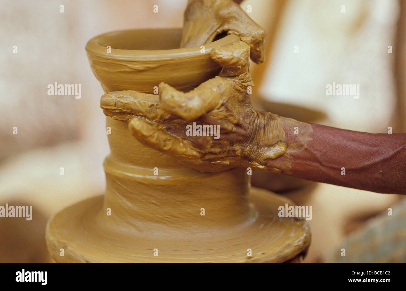 With dextrous fingers a Potter turns clay on a kick pottery wheel. - Stock Image