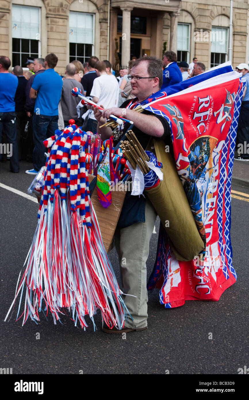 Street Vendor selling banners and flags at an Orange Walk Parade through Glasgow city centre, Scotland, UK - Stock Image
