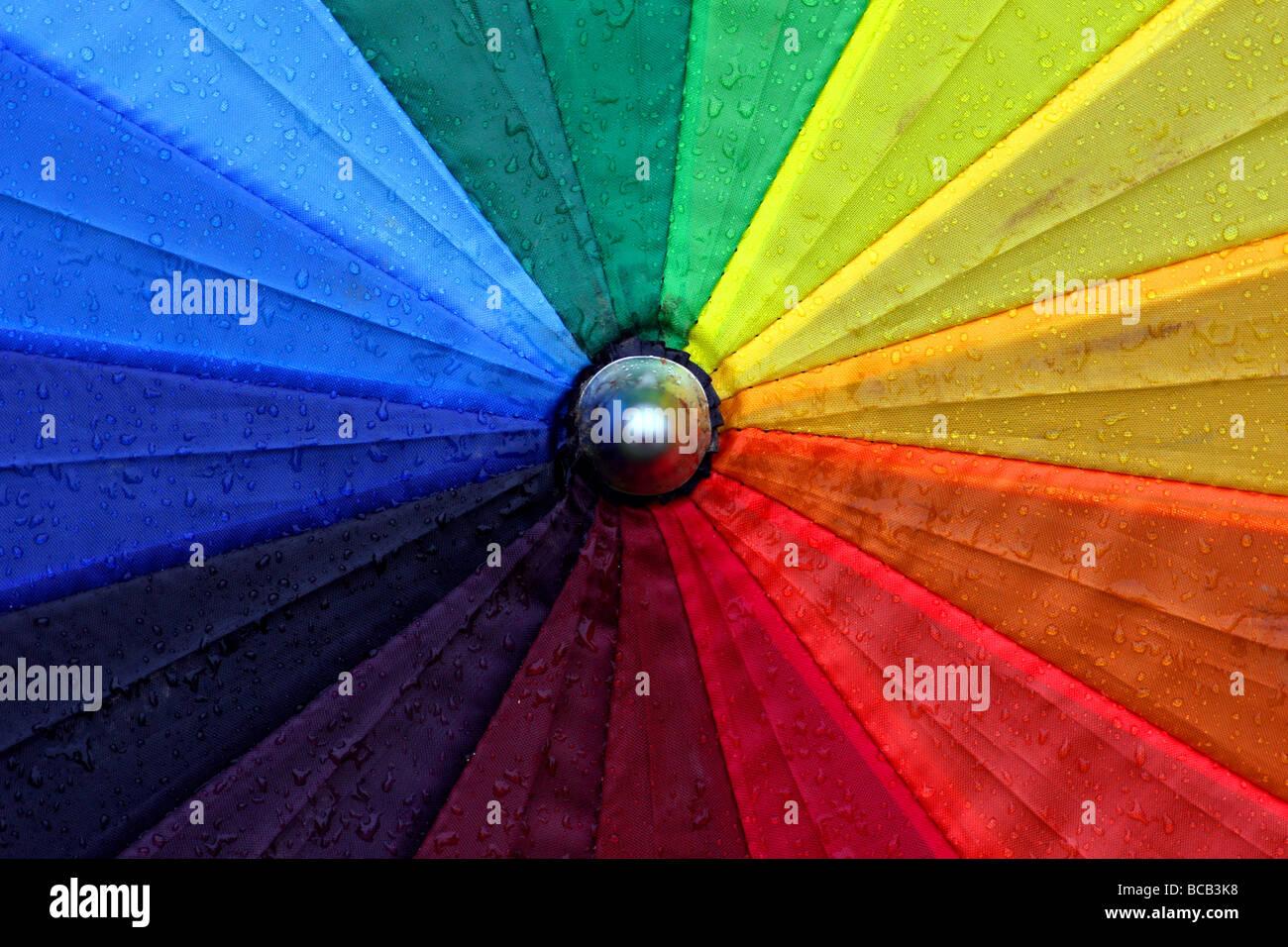 Multicoloured umbrella in rain - Stock Image